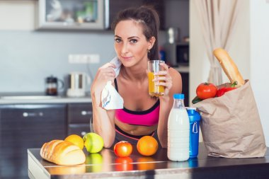Pretty attractive athletic active sportive lady woman standing in kitchen with a towel on her shoulder and healthy food fresh fruits milk bread drinking juice