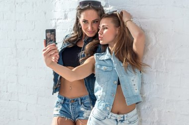 Girls friends taking selfie picture. Two beautiful young women having fun making photo and grimacing with mobile phone