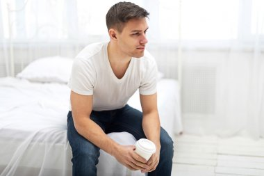Handsome man guy in white T-shirt and blue jeans sitting on bed with a cup of morning coffee.