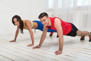 Training. Beautiful girl and handsome guy workout together making push ups on the white wooden floor