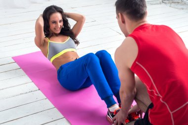 athletic sporty couple friends. Woman doing crunches abdominal exercises on floor in gym with a help of guy concept training exercising workout fitness aerobic