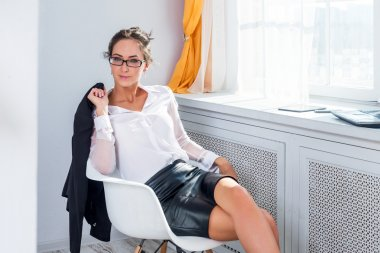 Attractive young businesswoman in glasses sitting on the chair next to window with jacket her hands.