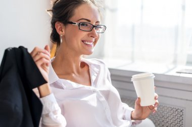 Smiling young woman in glasses with the cup of coffee or tea her hands sitting near window.