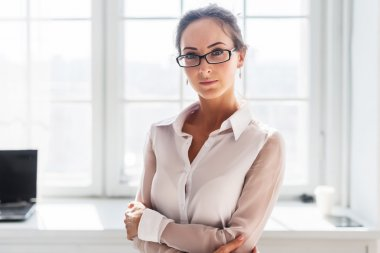 Serious young businesswoman in glasses standing front of the window background arms crossed