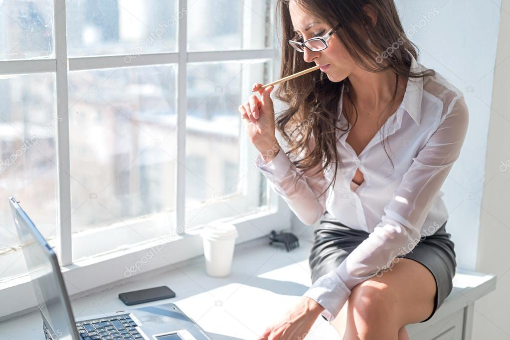 Businesswoman sitting next to the window in front laptop notebook with pencil office