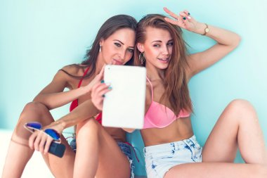 Two attractive beautiful young women in summer outfit street urban casual style having fun  taking self-portrait picture photos with the tablet sitting on ground red bikini bra swimsuit sunny day