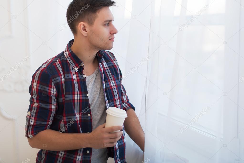 Chico guapo de hombre sonriente en camisa a cuadros mirando por la ventana con una taza de caf - Cuadros guapos ...