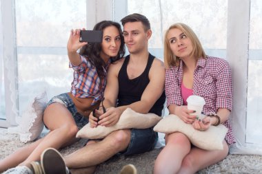 two girls and guy friends taking selfie together wearing summer clothes  jeans shorts jeanswear street urban casual style having fun at home