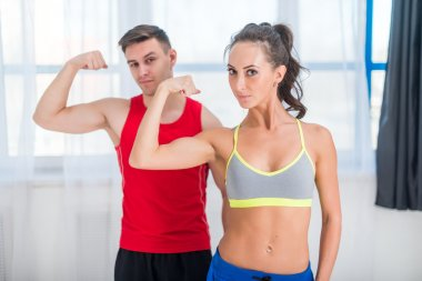 Active athletic sportive woman girl and man showing their muscles biceps healthy lifestyle looking at camera