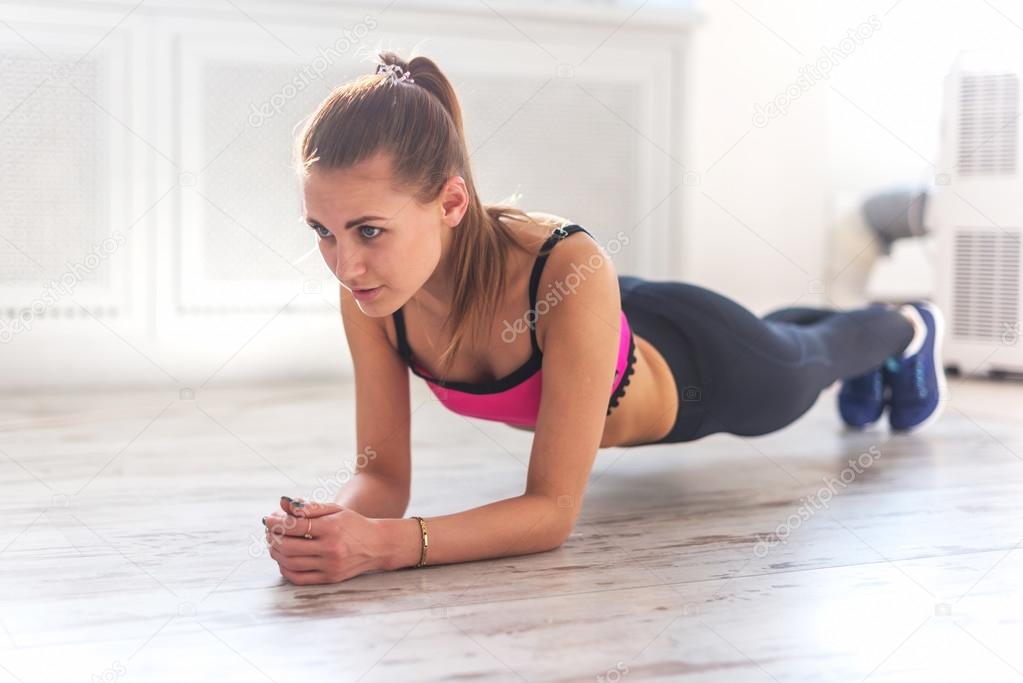 Slim fitnes young girl with ponytail doing planking exercise indoors at home gymnastics