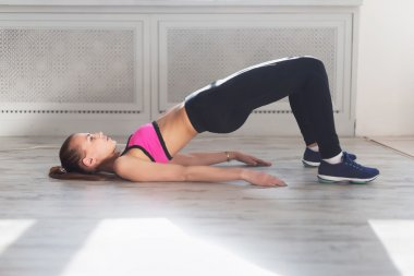 Side view of young woman doing gymnastics the half bridge pose in fitness studio or home practices yoga warming up exercises for spine, backbend, strengthening back and shoulders muscles