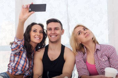Happy friends two women and man taking selfie with camera or smartphone together wearing summer clothes  jeans shorts jeanswear street urban casual style having fun.