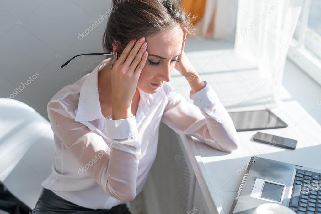 Portrait of tired young business woman suffering from headache in front laptop at office desk