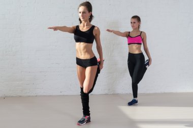 women doing stretching exercises warm up standing on one leg outstretched arm in front of her