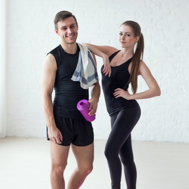 Portrait of a athletic man after doing exercises sportsman holding towel and shaker protein cocktail or bottle with water