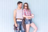 Fotografie Happy couple friends wearing sunglasses in summer jeanswear street urban casual style talking having fun standing near wall
