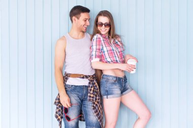 Happy couple friends wearing sunglasses in summer jeanswear street urban casual style talking having fun standing near wall