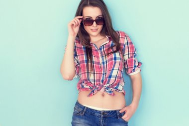 Outdoor summer closeup portrait of young stylish fashion glamorous woman in shirt and denim shorts sunglasses standing on the blue background