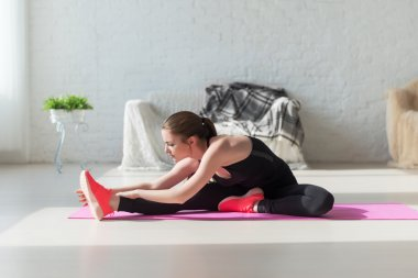Fit woman high body flexibility stretching her leg to warm up doing aerobics gymnastics exercises at home