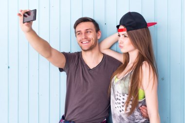 Couple friends taking selfie together wearing summer clothes  jeans shorts jeanswear street urban casual style having fun.