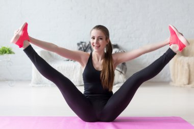 Funny smiling girl holding legs apart doing exercises aerobics warming up with gymnastics for flexibility leg stretching workout at home fitness.