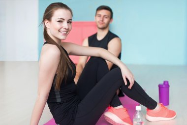 sporty couple friends athletic woman and man sportsmen in sport gym sitting floor looking at camera