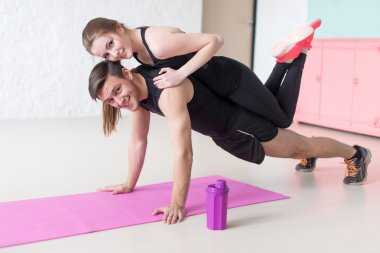 man doing push ups with woman laying on back at gym or home smiling looking camera concept fitness sport training teamwork and lifestyle
