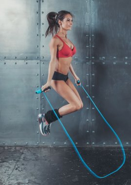 Sporty woman jumping skipping rope concept sport health fitness loss weight cardio training workout wellness.