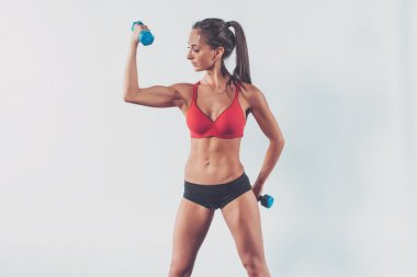 athletic woman pumping biceps doing workout lifting up dumbbell exercise for arm muscles fitness, sport, training diet lifestyle concept