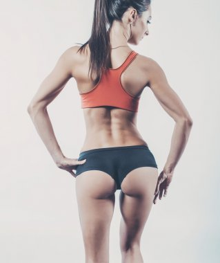Muscular active athletic young woman with sexy buttocks posing showing muscles of the back shoulders and hands fitness, sport, training diet lifestyle concept.
