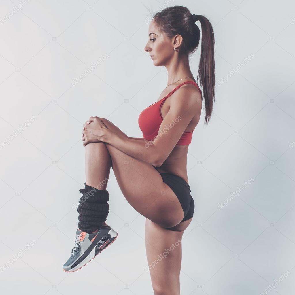 Portrait of muscular active athlete woman standing looking forward lifting up leg in hands doing exercise warming working stretching with fitness, sport, training and lifestyle concept