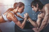 Fotografie Athlet muskulöse Sportler Mann und Frau mit Händen verschränkt Armdrücken Herausforderung zwischen ein junges paar Crossfit Fitness Sport Training Lifestyle Bodybuilding-Konzept