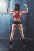 Svalnatý aktivní sportovní mladá žena ukazuje svaly zadní ramena a ruce fitness, sport, životní styl koncepce školení.