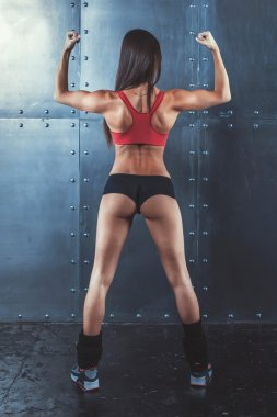 Muscular active athletic young woman showing muscles of the back shoulders and hands fitness, sport, training lifestyle concept.