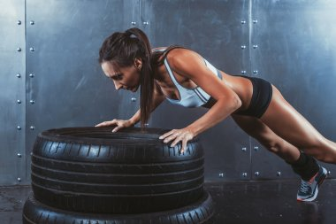 Sportswoman. Fit sporty woman doing push ups on tire strength power training concept crossfit fitness workout sport and lifestyle.
