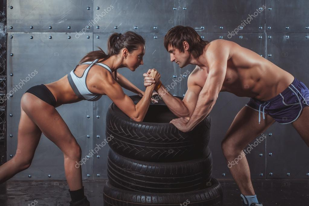 Athlete muscular sportsmen man and woman with hands clasped arm wrestling challenge between a young couple Crossfit fitness sport training lifestyle bodybuilding concept.
