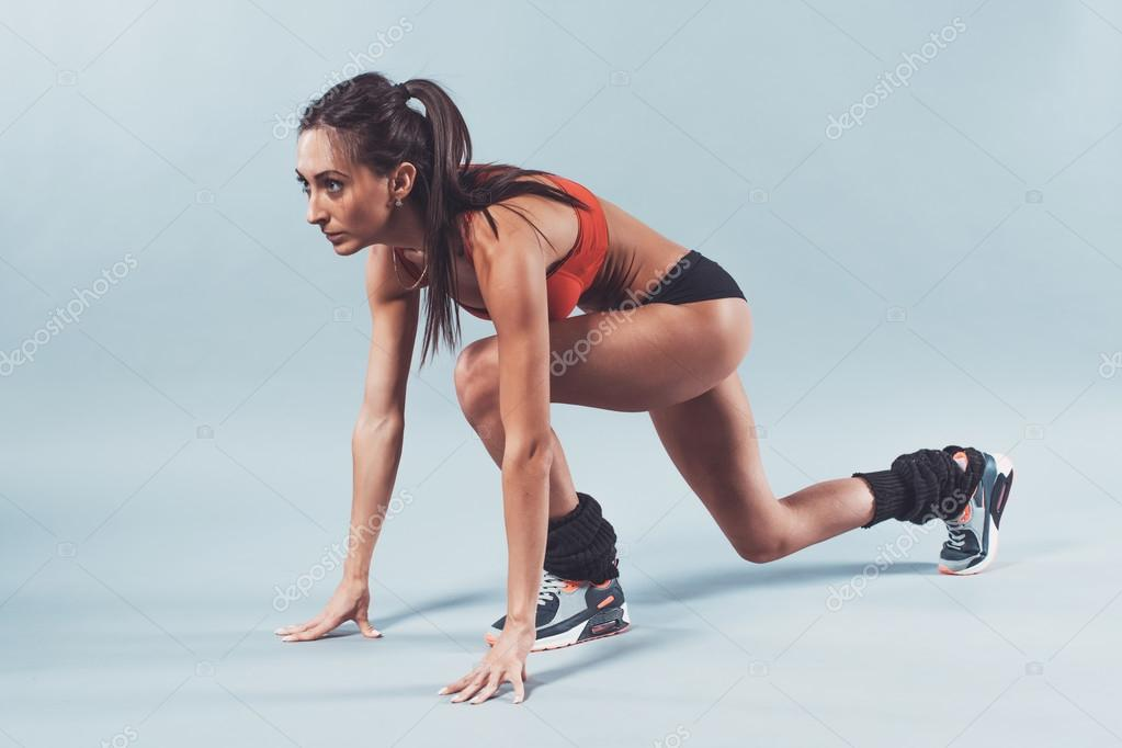 Sportive athlete woman sprinter waiting for the start running position fitness, sport, training and lifestyle concept