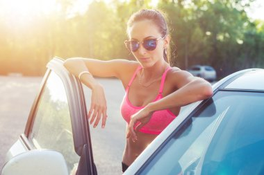 Athlete sporty fit young woman in sports bra wearing sunglasses standing leaning on car with door open looking at camera.