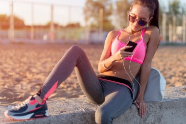 Beautiful fitness athlete woman wearing sunglasses resting listening music after work out exercising on summer evening in beach at sunset with smartphone outdoor portrait.