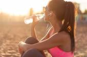 Fotografie Beautiful fitness athlete woman drinking water after work out exercising on sunset evening summer in beach outdoor portrait.