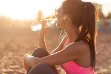 Beautiful fitness athlete woman drinking water after work out exercising on sunset evening summer in beach outdoor portrait.