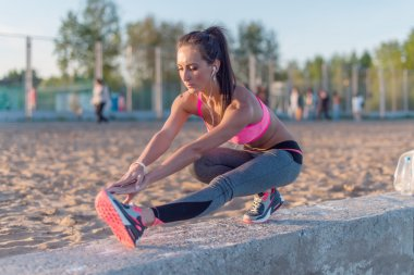 Athletic woman stretching her hamstring, legs exercise training fitness before workout outside on a beach at summer evening with headphones listening music.