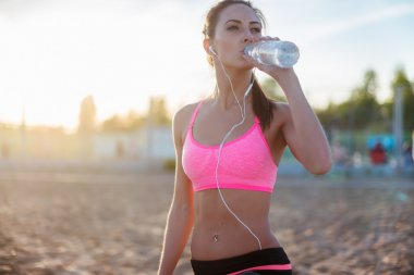 Beautiful fitness athlete woman resting drinking water after work out exercising on beach summer evening in sunny sunshine outdoor portrait