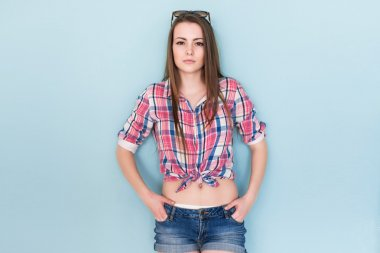 Outdoor summer closeup portrait of young stylish woman in shirt and denim shorts sunglasses standing on the blue background