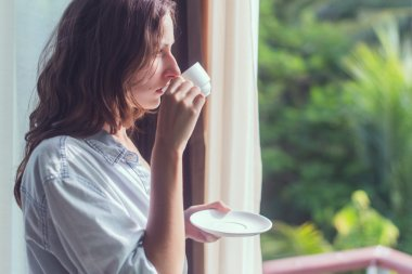 Woman drinking tea or coffe and looking through the window.  Young lady meeting sunrise.