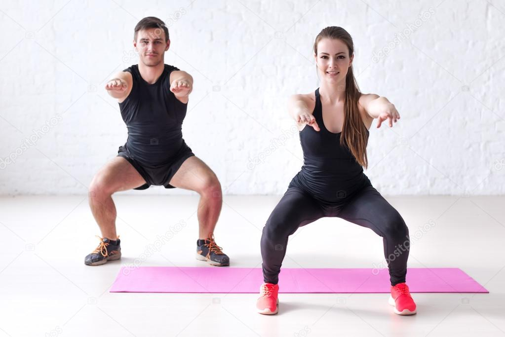 Fitness man and woman exercising squat exercise hands behind head looking at camera concept sport, training, warming up lifestyle