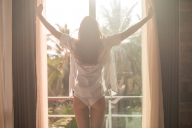 Lovely woman is awoke and standing before window. Girl opening curtains meeting sunrise.