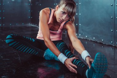 Fit woman doing stretching exercises her muscles back and legs before a training warm up at gym concept fitness, sport, lifestyle.
