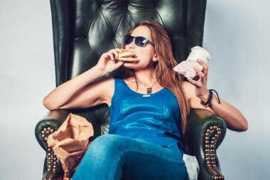 Funny crazy woman eating hamburger junk food and fries sitting in chair.