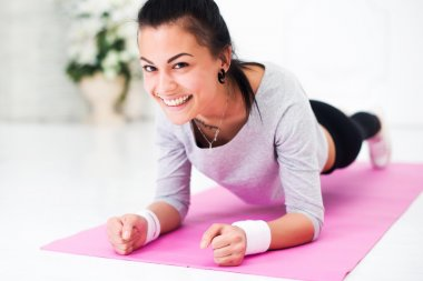 Pretty smiling young woman doing plank abdominal exercise at home in white room looking camera concept healthy lifestyle sport fitness